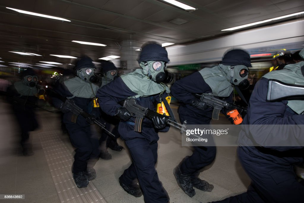 Police officers wearing gas masks participate in an anti-terror drill on the sidelines of the Ulchi Freedom Guardian (UFG) military exercises at a subway station in Seoul, South Korea, on Tuesday, Aug. 22, 2017. North Korea warned the U.S. on Tuesday it will face 'merciless revenge' for ignoring Pyongyangs warnings over annual military drills with South Korea. Photographer: SeongJoon Cho/Bloomberg via Getty Images