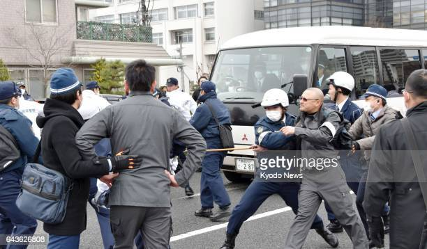 Police officers wearing helmets clash with protesters near the venue of the 12th annual 'Takeshima Day' ceremony held by the Shimane government in...