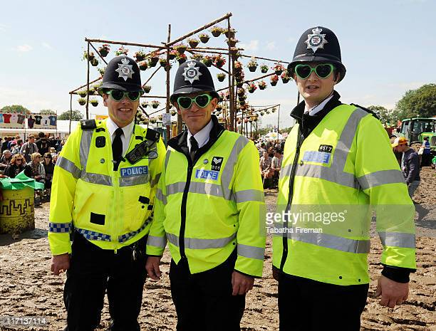 Police Officers wearing novelty sunglasses keep in with the festival atmosphere during the muddy but sunny first day of Glastonbury Festival at...