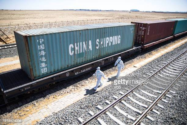 Police officers wearing personal protective equipment inspect a China-Europe Railway Express freight train at Erenhot Port on April 29, 2021 in...