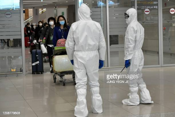 Police officers wearing protective clothing guide South Korean citizens repatriated from Italy to a bus at Incheon international airport, west of...