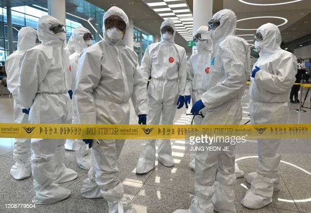 Police officers wearing protective clothing wait to guide South Korean citizens repatriated from Italy to a bus at Incheon international airport west...