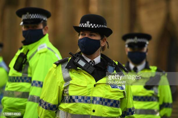 Police officers wearing protective face coverings to combat the spread of the coronavirus covid-19 oversee an anti-vax rally protest against...