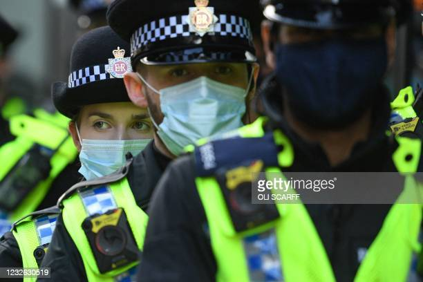 Police officers wearing protective face coverings to combat the spread of the coronavirus, arrive to disperse the crowd of demonstrators protesting...
