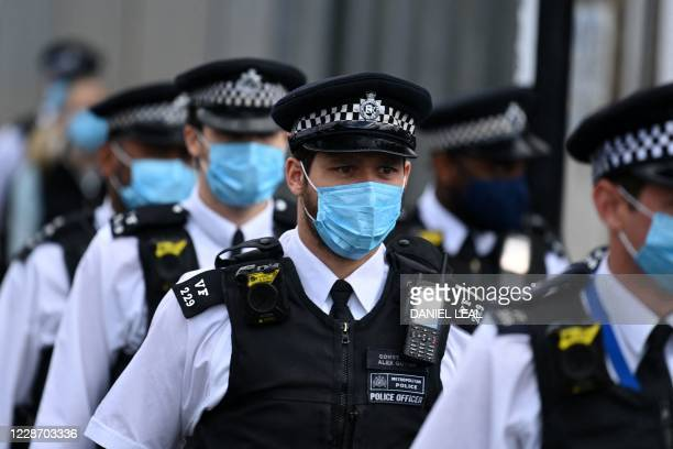 Police officers wearing protective face masks, arrive to pay their respects at the Croydon Custody Centre in south London on September 25 following...