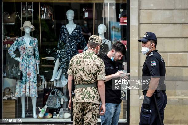 Police officers wearing protective face masks check documents of a man in Baku on June 21 amid the outbreak of COVID-19, caused by the novel...