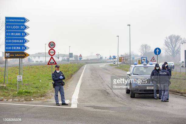 Police officers wearing protective face masks patrol a yellow zone quarantine roadblock near the quarantine red zone in the town of Codogno in...