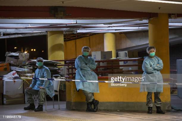 Police officers wearing protective gear stand guard behind cordon tape at Cheung Hong Estate in the Tsing Yi district of Hong Kong, China, in the...