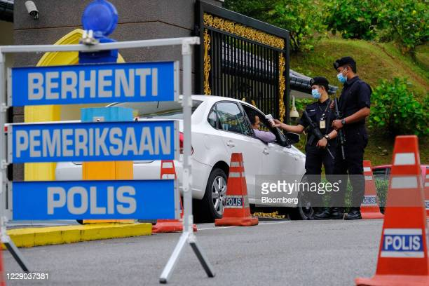 Police officers wearing protective masks check the temperature of a motorist entering the main entrance of the Istana Negara palace in Kuala Lumpur...