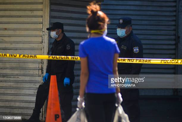Police officers wearing protective masks observe a woman carrying groceries on March 23 2020 in San Salvador El Salvador Three cases of COVID19 have...