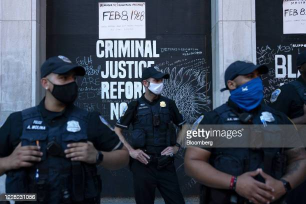 Police officers wearing protective masks stand in front of a criminal justice reform sign during the Republican National Convention in Washington,...