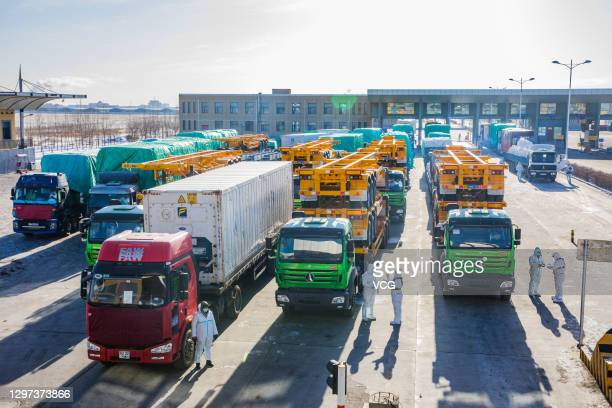 Police officers wearing protective suits check vehicles at Erenhot Port, the largest land port on the border between China and Mongolia, on January...