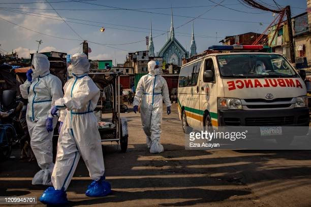 Police officers wearing protective suits go around a slum area to fetch residents suspected of having COVID-19 to be taken to an isolation facility...
