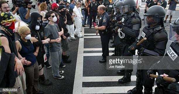 Police officers wearing riot gear keep protesters in check during a demonstration against the G8 Summit that is being held at nearby Sea Island June...