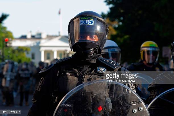 Police officers wearing riot gear push back demonstrators outside of the White House June 1 2020 in Washington DC during a protest over the death of...
