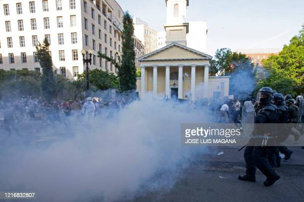 TOPSHOT Police officers wearing riot gear push back demonstrators shooting tear gas next to St John's Episcopal Church outside of the White House...