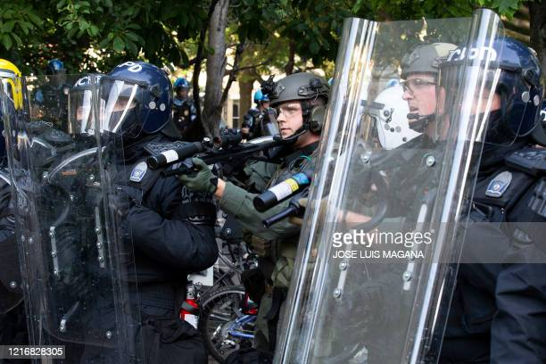 Police officers wearing riot gear shoot rubber bullets to demonstrators outside of the White House June 1 2020 in Washington DC during a protest over...