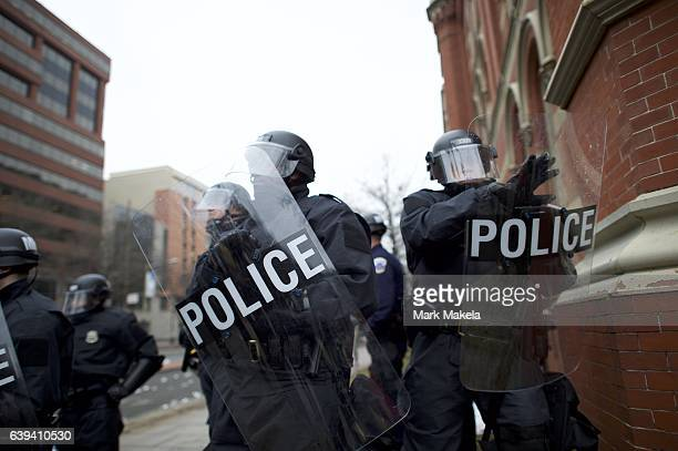 Police officers wearing tactical gear form a barrier with riot shields to prevent the movement of protestors after the inauguration of Donald Trump...