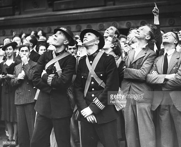 Police officers William Austin and Frederick J Read among a crowd of spectators watching the clock of Big Ben, London, as it strikes 11 o'clock on...