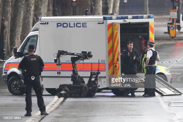 Police officers with a bomb disposal robot are seen on Victoria Embankment opposite Scotland Yard police headquarters in central London on October...