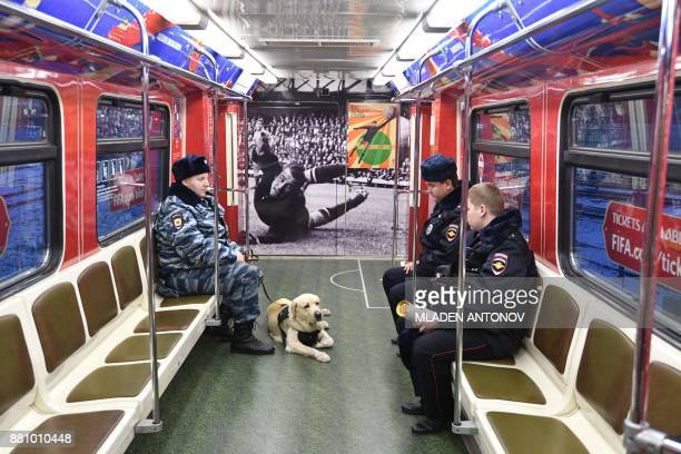 TOPSHOT Police officers with a dog ride in a FIFA 2018 World Cup themed metro train after the unveiling of the football tournament's official poster...