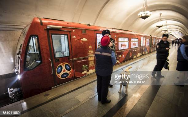 TOPSHOT Police officers with a dog stand on a platform near a FIFA 2018 World Cup themed metro train at Krasnopresnenskaya station in Moscow on...