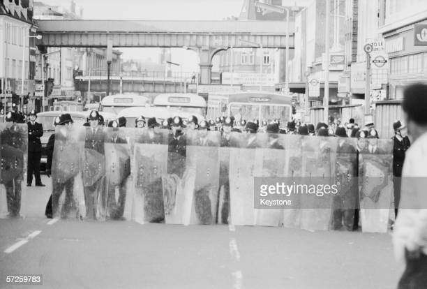 Police officers with riot shields block Brixton Hill on the second day of riots in Brixton London 13th April 1981