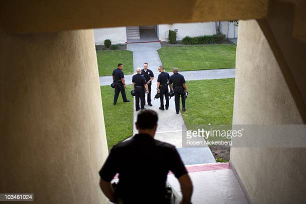 Police officers with the Los Angeles Police Department's gang unit search a second floor apartment for 600 rounds of stolen police ammunition and...