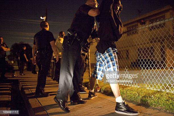 Police officers with the Los Angeles Police Department's gang unit search a group of men drinking in public outside the Jordan Downs Housing Project...