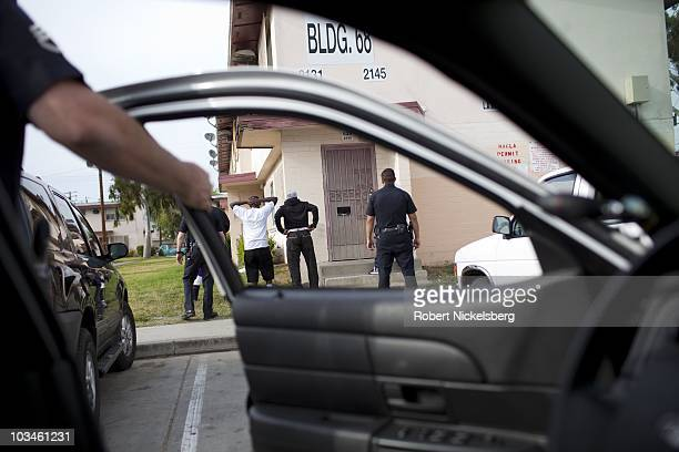 Police officers with the Los Angeles Police Department's gang unit search four young men in the Jordan Downs Housing Project April 15 2010 in the...
