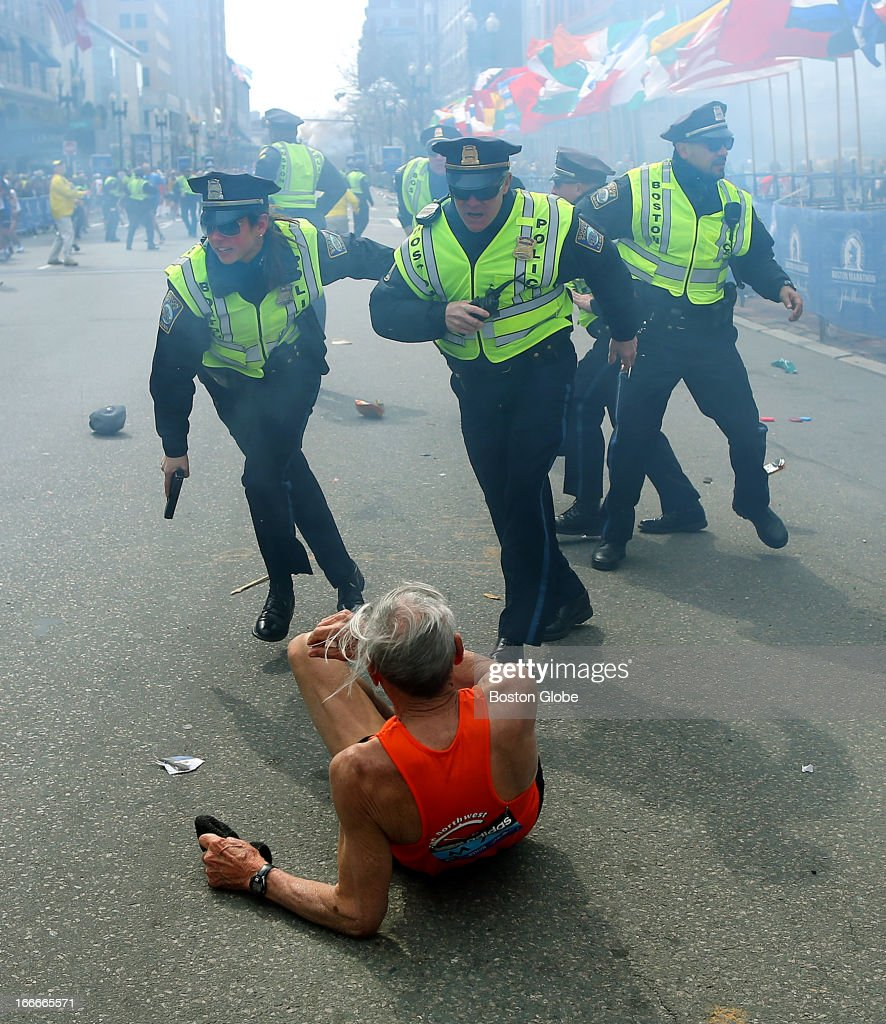 Police officers with their guns drawn hear the second explosion down the street. The first explosion knocked down 78-year-old US marathon runner Bill Iffrig at the finish line of the 117th Boston Marathon.