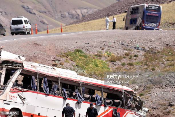 Police officers work at the scene after a bus carrying teenagers from a Chilean football school crashed into another bus on its way to Paraguay near...