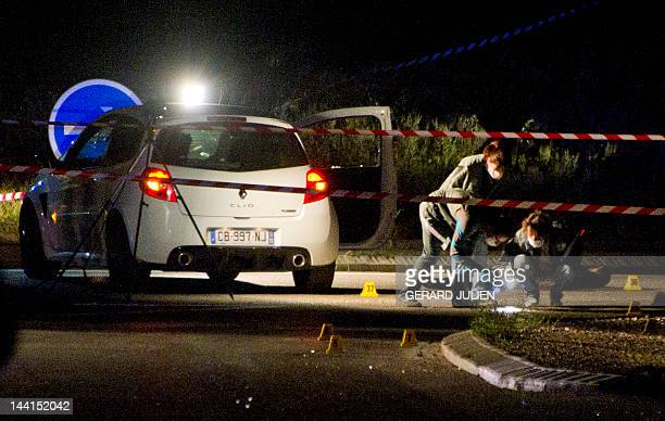 Police officers work on the scene where a man was found shot dead next to a car on May 10 2012 in GignaclaNerthe nearest Marseille southern France...