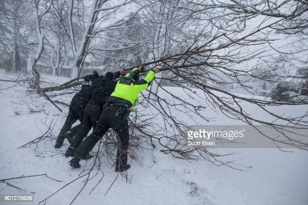 Police officers work to clear a downed tree as a massive winter storm bears down on the region on January 4 2018 in Scituate Massachusetts The 'bomb...