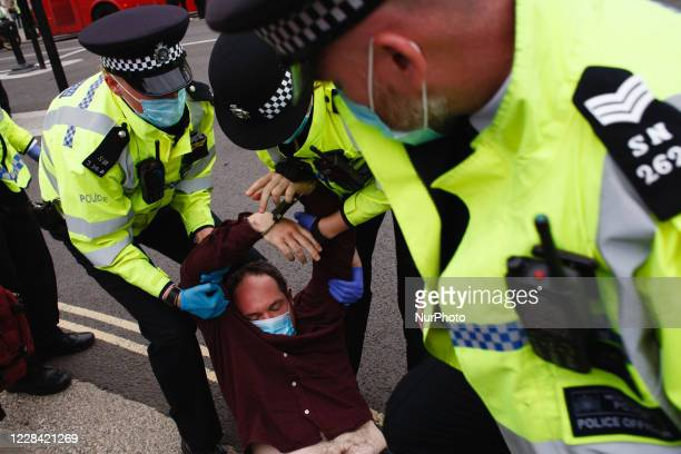 Police officers work to lift an arrested and handcuffed member of climate change activist movement Extinction Rebellion in Parliament Square in...