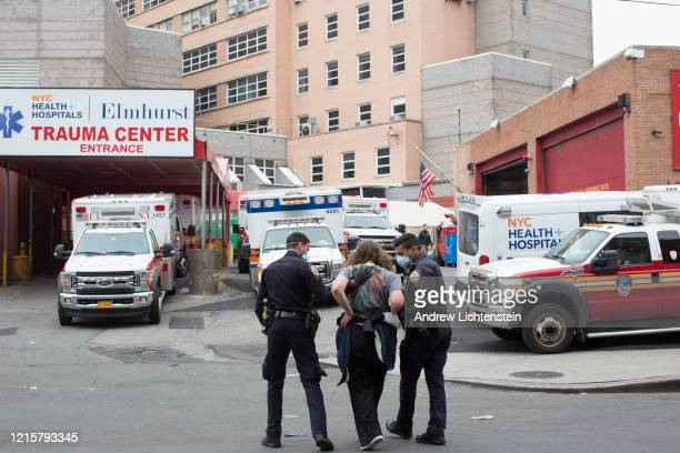 Police officersescort someone they have arrested to Elmhurst Hospital on March 30 2020 in Queens New York