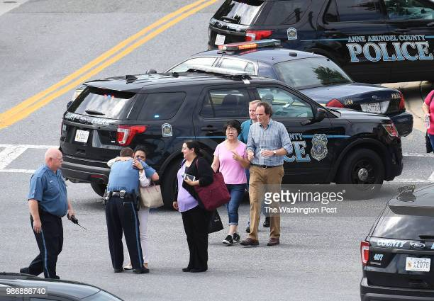 A police official hugs a woman walking from the direction of a building where a shooting took place at the Capital Gazette on Thursday June 28 2018...