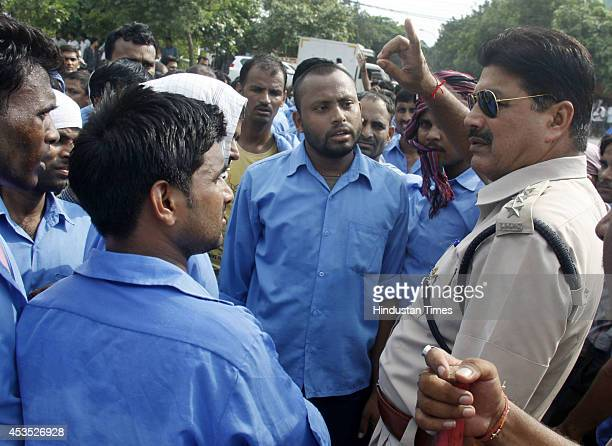 Police official talks with employees of Hero MotoCorp company who are protesting outside company gate on August 12 2014 in Gurgaon India The workers...