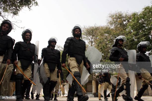 Police officials stand guard during rally of Islamic political party JamateIslami shout slogans against the US embassy in Islamabad for organizing...