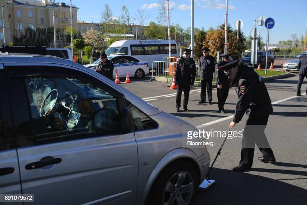 A police offier uses a mirror to check the underside of an automobile at a security entrance during the St Petersburg International Economic Forum at...