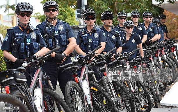 Police on bicycles form a barrier as they watch climate protesters at the G20 Finance Ministers and Central Bank Governors Meeting in Cairns on...
