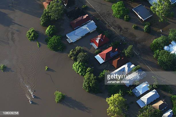 Police on jet skis patrol a flooded residential area on January 13 2011 in Brisbane Australia Twelve people have been confirmed dead in towns in the...