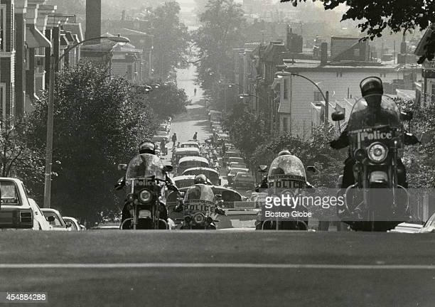 Police on motorcycles escort school buses carrying students on G Street in South Boston on Sept 11 1975 An initiative to desegregate Boston Public...