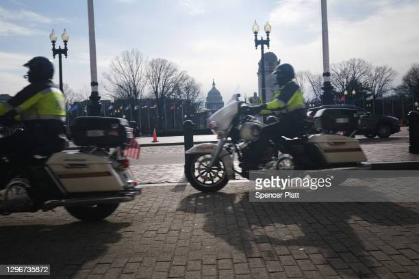 Police on motorcycles patrol past Union Station as it is under a high security lockdown in the days following the violent storming of the Capitol...