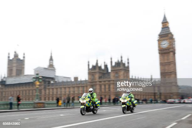 Police on motorcycles ride across Westminster Bridge away from the Houses of Parliament in central London on March 23, 2017 after the bridge reopened...