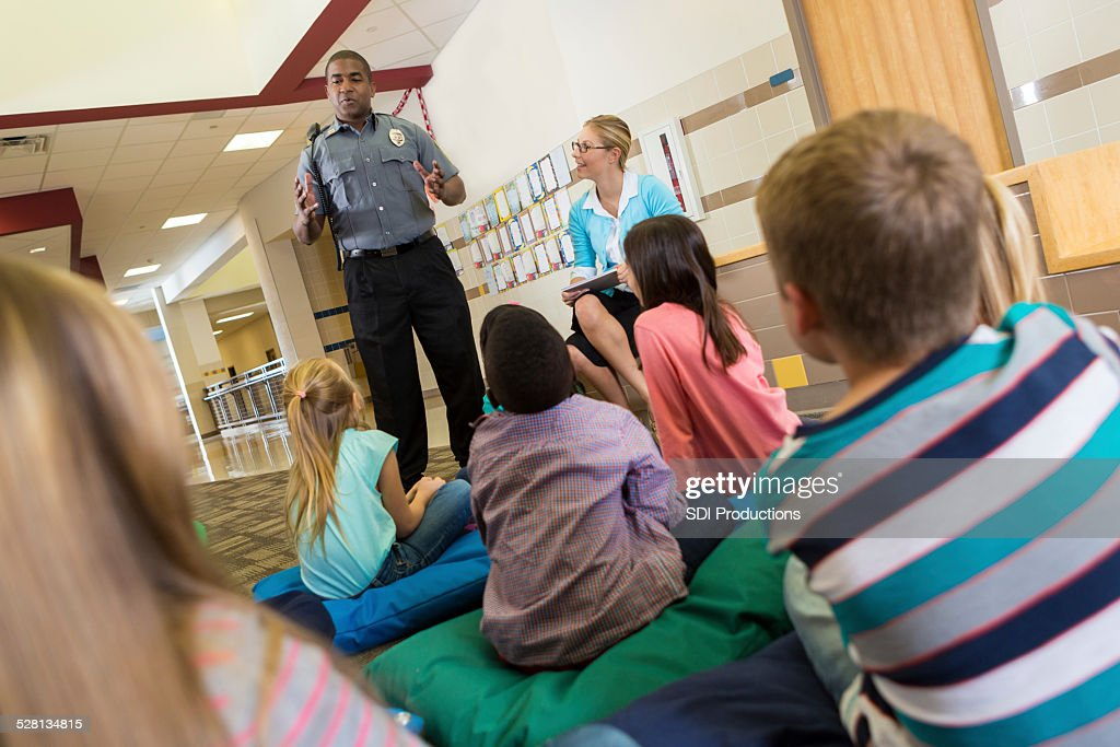 Police or school security officer speaking to young students : Stock Photo