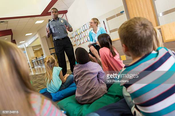 Police or school security officer speaking to young students