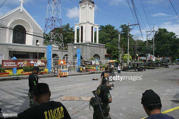 Police ordnance experts scour the road for clues after a powerful homemade bomb exploded outside a Catholic cathedral in Cotabato City southern...