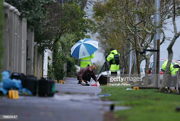 Police outside the scene as a resident cleans up where Augustine Akateuroa Borrell of Papatoetoe died after being stabbed in the chest in Hamilton...