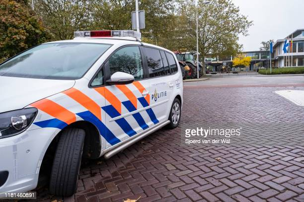 Police overlooking farmers parking their tractors on the side of the street in front of the Zwolle office of the Overijssel province in The...